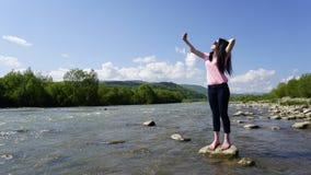Ritratto della giovane donna di fascino con i vetri rotondi che fanno selfie Fondo del fiume della montagna carpatica Immagini Stock Libere da Diritti