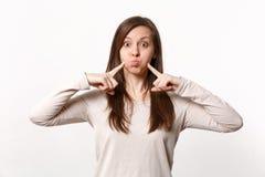 Ritratto della giovane donna divertente in vestiti leggeri che indica i dito indice sulle guance di salto isolate sulla parete bi immagini stock libere da diritti