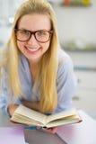 Ritratto della giovane donna felice che studia nella cucina Immagini Stock Libere da Diritti
