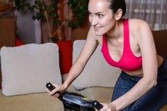 Ritratto della giovane donna felice sulla bici di esercizio Il concetto di forma fisica domestica Fotografia Stock