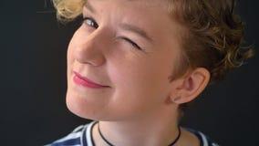Ritratto della giovane donna graziosa con capelli ricci che sorride e che lampeggia nella macchina fotografica, isolato su fondo  video d archivio