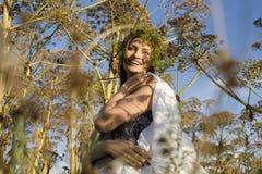 Ritratto della giovane donna graziosa nel campo con la natura enjoing dell'alta erba Fotografia Stock Libera da Diritti