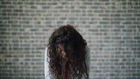 Ritratto della giovane donna malata che starnutisce esaminando macchina fotografica sul fondo del muro di mattoni video d archivio