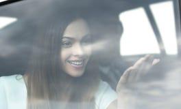 Ritratto della giovane donna nell'automobile dietro la finestra fotografia stock