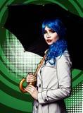 Ritratto della giovane donna nello stile comico di trucco di Pop art Femmina con l'ombrello sul fondo verde del fumetto immagini stock