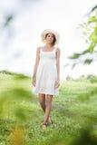Ritratto della giovane donna in prendisole e del cappello che camminano nel parco Fotografia Stock