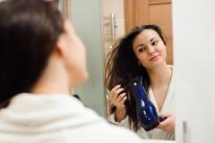 Ritratto della giovane donna prety che usando hairdryer immagini stock libere da diritti