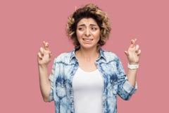 Ritratto della giovane donna promettente con l'acconciatura riccia nella condizione blu casuale della camicia con le dita attrave immagini stock