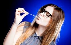 Ritratto della giovane donna rigorosa con i vetri della nullità e la gomma da masticare Immagini Stock