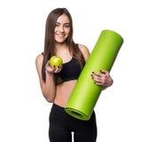 Ritratto della giovane donna sorridente che giudica la stuoia acciambellata di yoga di esercizio e mela verde isolate su fondo bi Fotografia Stock