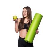 Ritratto della giovane donna sorridente che giudica la stuoia acciambellata di yoga di esercizio e mela verde isolate su fondo bi Fotografie Stock Libere da Diritti