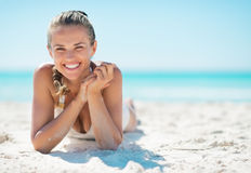 Ritratto della giovane donna sorridente che mette su spiaggia immagini stock