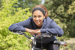 Ritratto della giovane donna sorridente che si esercita con la bicicletta, all'aperto Fotografia Stock