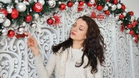 Ritratto della giovane donna sorridente graziosa che gode della decorazione di natale con le palle bianche e rosse archivi video