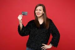 Ritratto della giovane donna sorridente sbalorditiva in maglione nero della pelliccia che giudica la carta assegni di credito iso immagine stock libera da diritti