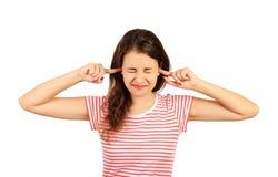 Ritratto della giovane donna sottolineata arrabbiata che tappa strettamente le orecchie con le dita e gli occhi di closing ragazz Immagine Stock