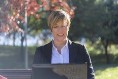Ritratto della giovane donna sveglia sorridente che lavora con il computer portatile all'aperto Fotografie Stock