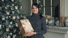Ritratto della giovane signora affascinante con la condizione del contenitore di regalo vicino all'albero di Natale e l'esame dec video d archivio