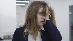Ritratto della giovane signora stanca triste in vestiti convenzionali che afferra i suoi capelli e distoglie lo sguardo e giù,  stock footage