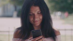 Ritratto della giovane signora in un parco di estate che legge un messaggio di testo sul suo Smart Phone Bella ragazza con capell video d archivio