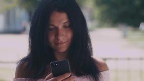 Ritratto della giovane signora in un parco di estate che legge un messaggio di testo sul suo Smart Phone Bella ragazza con capell archivi video