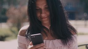 Ritratto della giovane signora in una via della città di estate facendo uso dello smartphone video d archivio