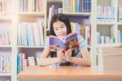 Ritratto della lettura dello studente e della ricerca asiatiche abili fare Immagini Stock