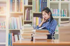 Ritratto della lettura dello studente e della ricerca asiatiche abili fare Immagine Stock