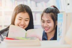 Ritratto della lettura dello studente e della ricerca asiatiche abili fare in c Immagine Stock