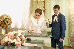 Ritratto della licenza di nozze di firma della bella sposa alla registrazione Fotografia Stock