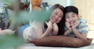 Ritratto della madre asiatica e del figlio della famiglia che esaminano macchina fotografica e che agiscono insieme sul vostro fr stock footage