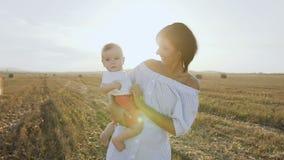 Ritratto della madre caucasica felice che tiene il suo piccolo figlio, lei che gioca con il bambino nel campo al tramonto felice video d archivio