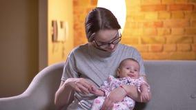 Ritratto della madre che abbraccia sua figlia neonata sveglia che si siede sul sofà a nel salone video d archivio