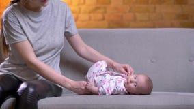 Ritratto della madre che gioca con sua figlia neonata sveglia che si trova sul sofà nel salone archivi video
