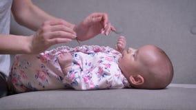 Ritratto della madre che segna sua figlia neonata sveglia che si trova sul sofà nel salone stock footage