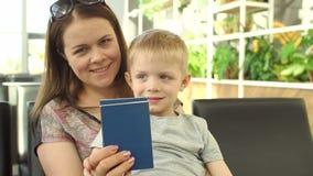 Ritratto della madre con il bambino all'aeroporto con i passaporti ed i biglietti a disposizione video d archivio