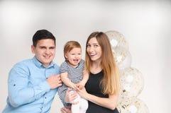 Ritratto della madre, del padre e della figlia felici sulla sua prima festa di compleanno Fotografia Stock