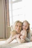 Ritratto della madre felice e della figlia che si trovano sul pavimento a casa Fotografie Stock