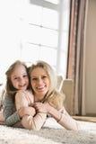 Ritratto della madre felice e della figlia che si trovano sul pavimento a casa Immagini Stock