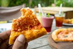 Ritratto della mano con il morso di uno sguardo della pizza della fetta uno squisito con formaggio giallo fotografia stock