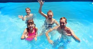 Ritratto della mano d'ondeggiamento della famiglia felice nella piscina video d archivio