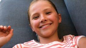 Ritratto della mano d'ondeggiamento della ragazza sveglia sul sofà video d archivio