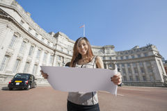 Ritratto della mappa felice della tenuta della giovane donna contro l'arco di Ministero della marina a Londra, Inghilterra, Regno Fotografie Stock