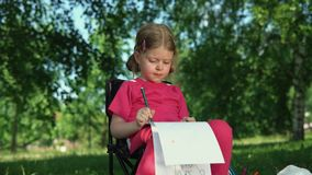 Ritratto della matita del disegno della bambina all'aperto di estate del parco video d archivio