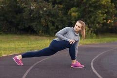 Ritratto della misura e della giovane donna sportiva che fanno allungamento nella p Immagini Stock