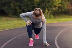 Ritratto della misura e della giovane donna sportiva che fanno allungamento nella p Immagini Stock Libere da Diritti