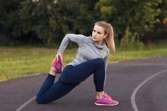 Ritratto della misura e della giovane donna sportiva che fanno allungamento nella p Fotografie Stock Libere da Diritti