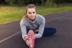 Ritratto della misura e della giovane donna sportiva che fanno allungamento nella p Fotografie Stock