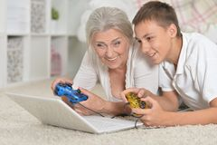 Ritratto della nonna e del nipote che giocano gioco di computer con il computer portatile fotografia stock libera da diritti