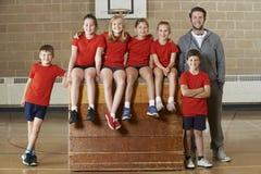 Ritratto della palestra Team Sitting On Vaulting Horse della scuola immagini stock